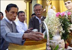Tin Oo prepares to pour water on a Buddha image during his visit to the Shwedagon Pagoda in Rangoon, Burma, a day after he was released from nearly seven years in detention.