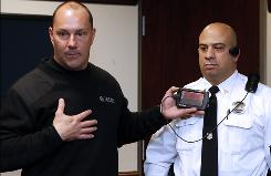 Clay Winn, left, with Taser International demonstrates a new portable camera for law enforcement on Phillip Buccino.