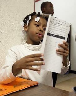 Six-year-old Sherwan Liddell starts on her homework at Chicago's Olive Branch Mission where she has lived since October with her mother Charrse Liddel and five siblings.