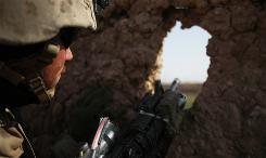 A U.S. Marine from 3rd Battalion, 6th Marine Regiment peers out from a hole in a wall of a compound in Marjah in Afghanistan's Helmand province on Tuesday.