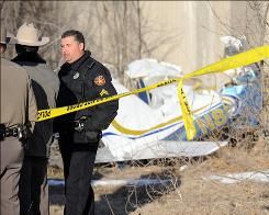 Texas Department of Public Safety Troops and Amarillo Police Department officers watch over the crash scene of a  plane into the Arctic Glacier Premium Ice building in Amarillo, Texas. Two Amarillo men in their 50s died Wednesday morning when the plane went down, Texas Department of Public Safety Trooper Gabriel Medrano said.