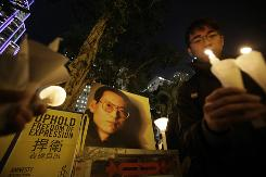Pro-democracy protesters in Hong Kong hold a candlelight vigil Tuesday to show support for recently jailed mainland dissident Liu Xiaobo. China gave Liu 11 years in prison after he helped write a political freedom petition.
