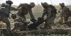 U.S. Army Staff Sgt. and flight medic Robert Cowdrey, of La Junta, Colo., far left, with Task Force Pegasus, coordinates a medical evacuation mission as Marine infantrymen carry a combative and wounded Taliban fighter captured minutes earlier, according to witnesses in Marjah on Wednesday.