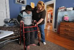 Derek Collette, 13, who has cerebral palsy, winces with pain as his mother Christina Collette helps lift him out of bed in the morning. Derek has been largely confined to a wheelchair and unable to go to school since he had the flu in May 2009.