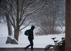 A student hurries through a passing snow squall on the campus at the University of Massachusetts in Amherst, Mass., Feb. 16. Private universities such as Amherst, NYU and USC have begun more actively recruiting transfer students from community colleges.