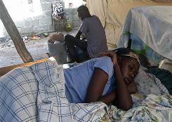 Maletid Desilien, 27, lies on a bed Saturday as a man washes in makeshift camp in Port-au-Prince. Ever since Desilien gave her four children, including a 3-month-old, to U.S. missionaries, she has been emotionally unstable, according to neighbors.