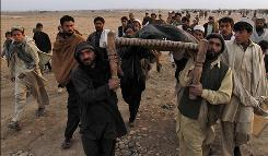 Afghan people carry the body of a civilian killed in a suicide bombing on a small group of tribal elders and government workers near Jalalabad on Monday.