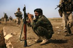 An Afghan soldier pauses near a market reopened by Marines on the outskirts of Marjah in Afghanistan.