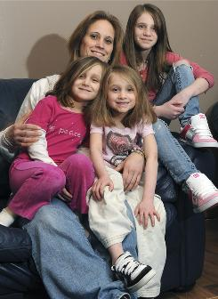 Plaintiff and single mom Doreen Flynn sits at home in Lewiston, Maine, with her three daughters: Jordan, 11, and 5-year-old twins Jorja, left, and Julia. All need bone marrow transplants.