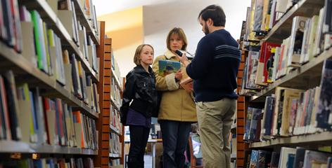 Librarian Bryan Hissong uses his Samsung Q1 Ultra tablet computer to assist Carleen MacDonald, 8, and Dawn Aluise as they search for the book Twilight at the Westminster Branch of the Carroll County (Md.) library.