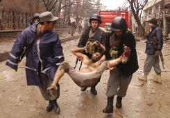 Afghan police officers carry a wounded man at the scene of an explosion at a guesthouse in Kabul on Friday.