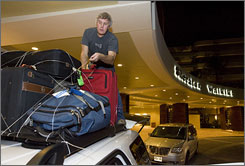 Dean Collins from Anderson, S.C., ties down his luggage to the roof of his car as he prepares to leave the Sheraton on Waikiki Beach after a tsunami warning was issued.