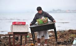 A man carries some of his belongings after a tsunami hit Pueco on Sunday.