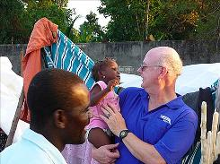 Volunteer Rich Pickett, right, plays with a child in Haiti during a furlough from his university job.