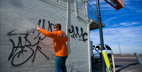Joe Bender spray-paints over graffiti at a convenience store in Avondale, Ariz. The city has struggled for years with graffiti and next month will enlist residents to download new software and help.