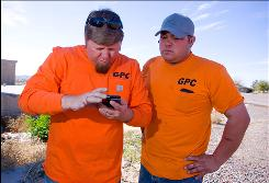 Graffiti removal technicians Joe Bender, left, and Jayson Branch get work orders through an iPhone.