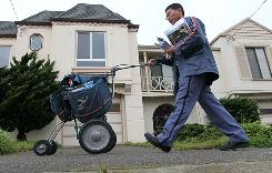 U.S. Postal Service lettercarrier Raymond Hou pushes a cart as he delivers mail along his route March 2, in San Francisco.