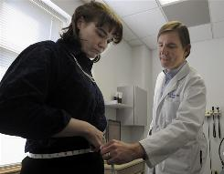 Eric Westman measures the waist of patient Jennifer Nolan at the Durham Medical Center in Durham, N.C. Westman is one of the authors of a new book, &quot;The New Atkins For a New You.&quot;  Nolan, who was pre-diabetic and over 200 pounds, has lost 70 pounds in a year, dropping from a size 22 to 10,  based on Westman's diet.