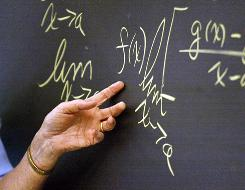 "A math teacher points to an equation on the blackboard during a high school calculus class. More teachers surveyed say their own self-evaluation would be a ""very accurate"" measure of teacher performance than parent evaluations, standardized tests, or principal review."