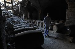 A man stands beside damaged wine barrels at the Santa Rita winery in Santiago, Chile, on Wednesday.