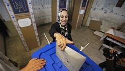 An Iraqi woman casts her vote for the parliamentary elections on Sunday in Baghdad, Iraq.