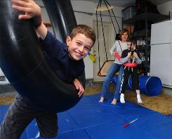 Kim Leserman and her sons, Jack, 9, left, and Brady, 6, spend time in their special gym inside their garage in Manhattan Beach, Calif. Both boys have been diagnosed with sensory processing disorder.