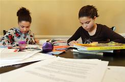 "Louisa Perry-Farr, 13, left, works on science, while her 10-year-old sister Thea Perry-Farr works on logic in the dining room of their Lexington, Ky., home. ""We're not religious home-schoolers, and there's somewhat of a feeling of being outnumbered,"" says Mia Perry."