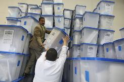 Iraqi workers in Baghdad store ballot boxes Monday following its general elections Sunday.