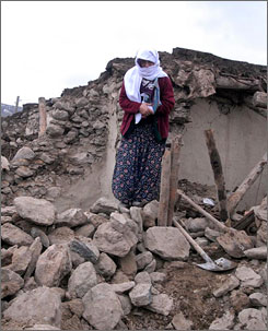 A woman stands in front of her destroyed house in the southeastern city Elazig.