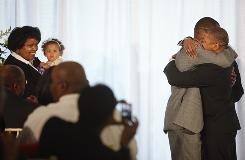 Rocky Galloway, left, is embraced by his new husband Reginald Stanley after being married on Tuesday, the first day that gay marriage is legal in Washington. One of the couples' twin daughters is held by Cherrie McCoy, left.