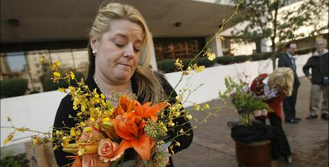 Plaintiff Monique Chauvin arranges flowers in front of the U.S. District Court in New Orleans.
