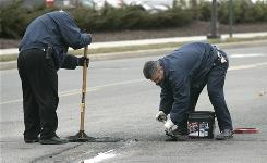 A work crew patches a pothole in Richmond, Va., on Feb. 26. Several snow storms in the Mid Atlantic have left roads laden with potholes.