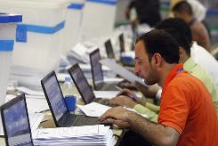 Iraqis tally votes at the Independent High Electoral Commission headquarters in Baghdad on Thursday.