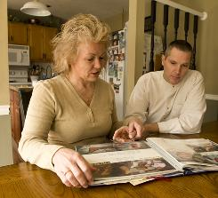 Johnna and Jeff Baskett look over a scrapbook they keep of their son, Marc, at home in Commerce, Ga. They didn't hesitate to enroll their son in the progesterone trial.