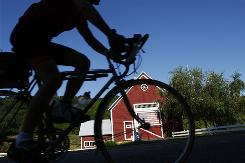A man bicycles past a colorful barn in South Pomfret, Vt. A new survey shows 40% of U.S. adults do no regular leisure-time physical activity.