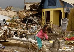 A girl removes debris in front of her earthquake destroyed house in Iloca, Chile, Sunday, March 14.