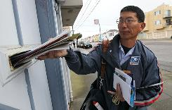 U.S. Postal Service lettercarrier Raymond Hou delivers mail along his route March 2 in San Francisco.