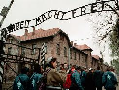 "File photo of April 22, 1998, shows young Israelis walking under the sign at Auschwitz concentration camp that means ""work sets you free."""