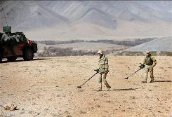Dutch soldiers of Charlie Air assault company check for unexploded bombs during a patrol in Chora valley in Afghanistan's southern Uruzgan province. By Deshakalyan Chowdury, AFP/Getty Images