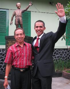 Barack Obama impersonator and Indonesian photographer Ilham Anas, right, and former Obama teacher Effendi, pose before a statue of a 10 year-old Obama at the government-run SDN Menteng 1 school (also known as the Besuki school) in Jakarta.