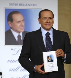 "Italian Premier Silvio Berlusconi shows the book ""Love always wins on envy and hatred"" during its launch in Rome on Friday."