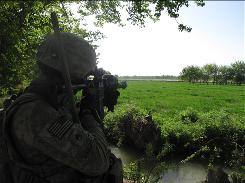 Staff Sgt. Jonathan Hughes watches for Taliban forces patrolling the other side of the Arghandab River.