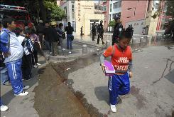 Police officers clean up the bloody crime scene outside an elementary school where a man allgedly stabbed 13 students in Nanping in southeast China's Fujian province Tuesday.