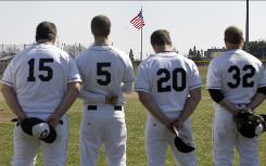 Goshen College baseball team members, left to right, Caleb Yoder, Lance Good, Clay Norris and Andy Swisher stand along the third base line for the singing of the national anthem in Goshen, Ind., on Tuesday. The national anthem was played at the school for the first time in its 116-year history.