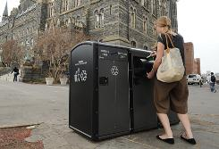 Kelly Melia-Teevan uses a solar-powered trash compactor on the Georgetown University campus in Washington, D.C.