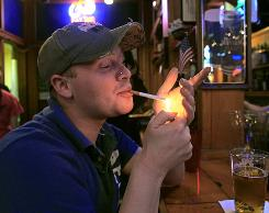 David Brathcher smokes a cigarette at Satisfaction Restaurant & Bar in Durham, N.C., on Dec. 17, shortly before a smoking ban in restaurants and bars took effect. At 45 cents, North Carolina is among states that have the lowest cigarette taxes per pack.