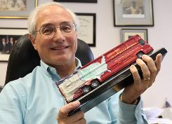 Sal Russo, the political activist who is the architect of the Tea Party Express, holds up a model of the bus in his office in Sacramento.