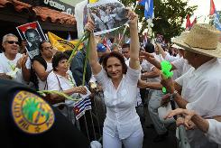 Singer Gloria Estefan holds a photo of Cuba's 'Las Damas de Blanco' as she marches Thursday in support of the opposition group. A similar rally is set for Sunday in Los Angeles.