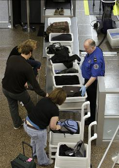 A TSA officer helps load items for X-ray at Seattle-Tacoma International Airport in January.