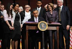 Surrounded by young people, President Barack Obama signs the Health Care and Education Reconciliation Act of 2010 at Northern Virginia Community College in Alexandria, Va., Tuesday, highlighting the measure included in the new law that overhauls student loan financing.